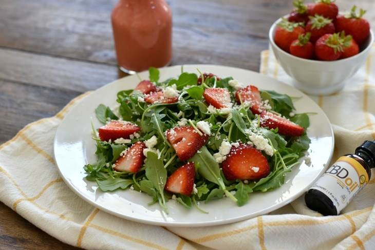 Strawberry Arugula Salad on a table with salad dressing.