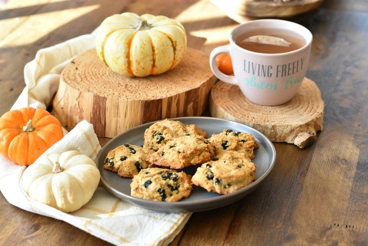 Cookies on a plate with pumpkins and a cup of tea on a table