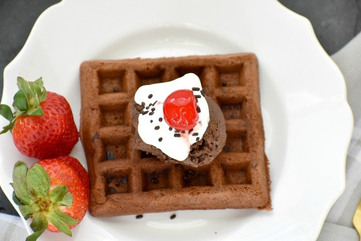 Paleo Chocolate Waffle on a plate with strawberries and whipped cream.
