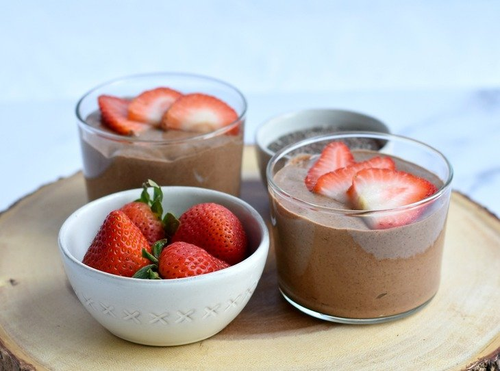 Chocolate chia pudding in clear bowls on a wood plate with strawberries in a bowl