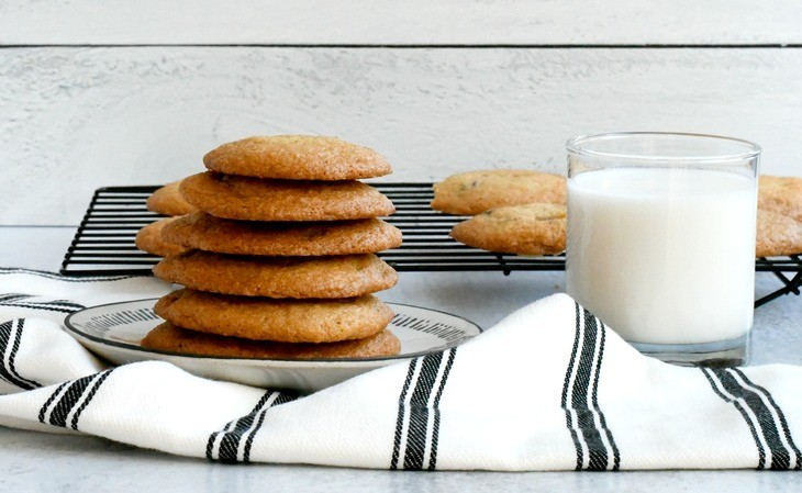 Gluten free cookies on a plate with a towel and a cup of milk