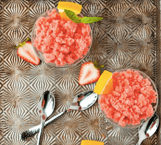 strawberry orange granita in bowls with spoons