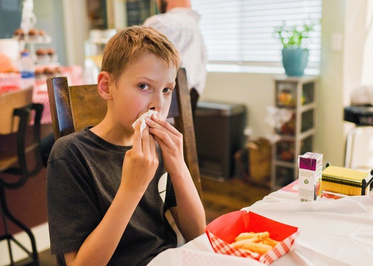 Boy eating and wiping his mouth
