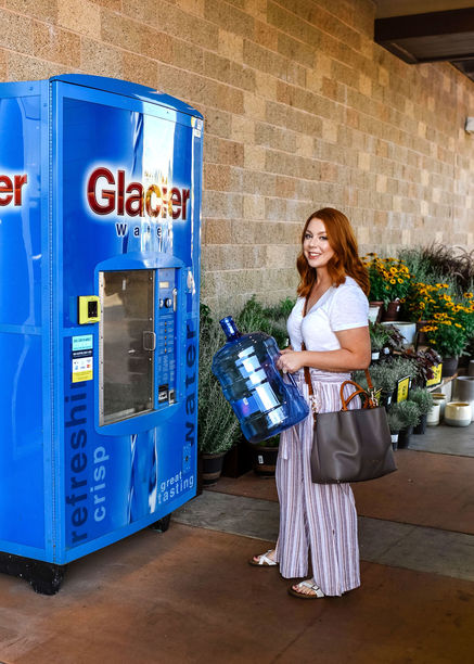 standing at the primo water refill station with 5 gallon jug