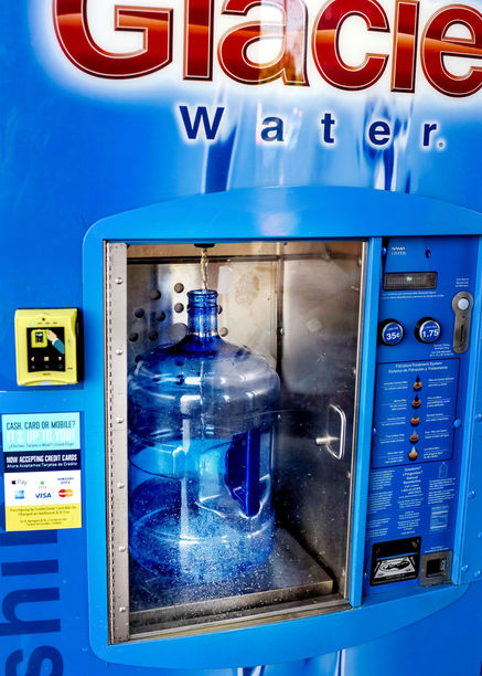 5 gallon jug being filled with water at refill station