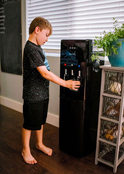 filling up a cup of water with the primo dispenser