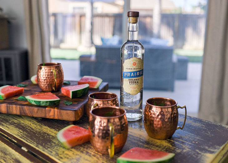 moscow mules on a table with prairie bottle and slices of watermelon