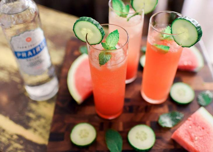 cucumber tonics on a table with slices of watermelon and cucumber