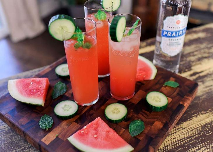 3 cucumber cocktails on a board with slices of watermelon and cucumber