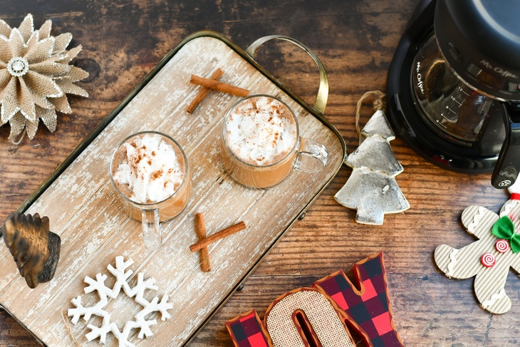 2 gingerbread lattes on a tray with christmas ornaments and coffee pot